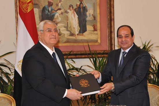 صورة الرئيس السيسى يسلم عدلى منصور النسخة الأولى من كتاب يوثق فترة رئاسته لمصر
