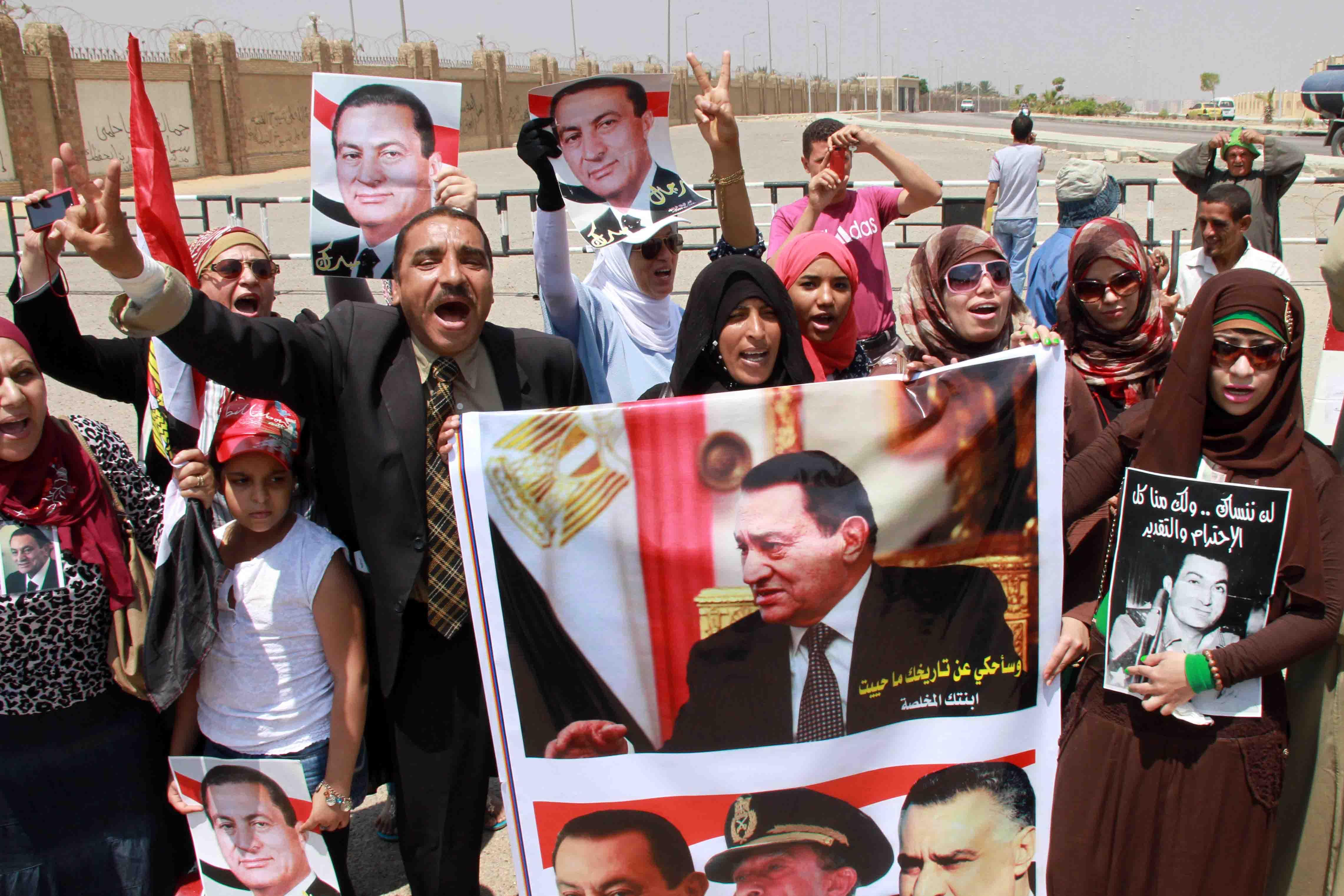 صورة أنصار مبارك يحرقون لافتة كتبوا عليها 25 يناير..وسط هتافات «عاش البطل المحارب»