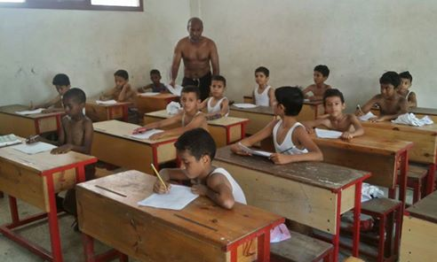 صورة طلاب مدرسة يمتحنون بدون قمصان لانقطاع الكهرباء وارتفاع الحرارة باليمن